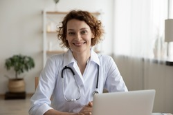 Portrait of smiling young Caucasian woman nurse sit at desk in hospital or private clinic, profile picture of happy positive female doctor GP in white medical uniform at workplace, healthcare concept