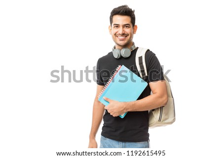 Portrait of smiling young college student with books and backpack against white background