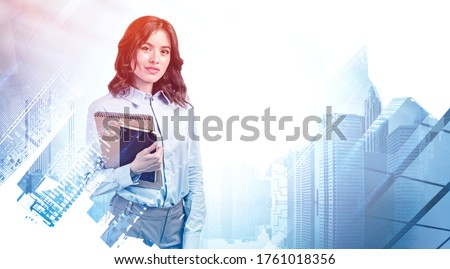 Portrait of smiling young European businesswoman or student with dark hair holding notebooks in blurry abstract city. Concept of education and leadership. Toned image double exposure Foto stock ©