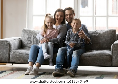 Portrait of smiling young family with little preschooler kids sit on couch in living room look at camera, happy caucasian parents relax on comfortable sofa at home enjoy time with small children
