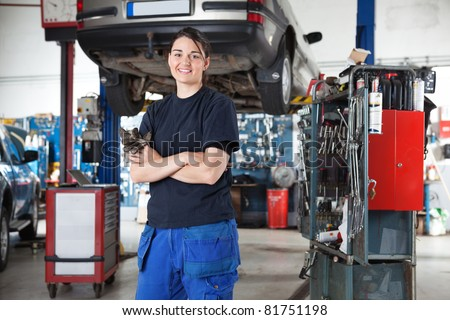 Portrait of smiling young female mechanic with arms crossed in auto repair shop
