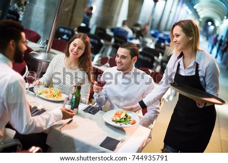 Portrait of smiling young friends in outdoors restaurant and smiling waitress