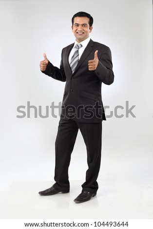 Portrait of smiling young indian business man giving thumbs up sigh with both hands