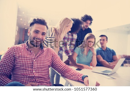 Portrait of smiling young informal businessman with colleagues in background at the office #1051577360
