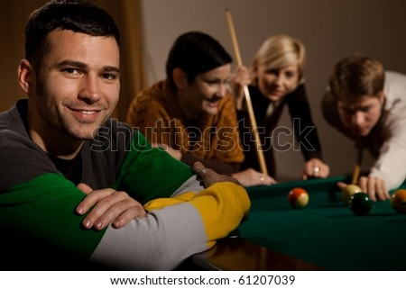 Portrait of smiling young man at snooker table, friends playing in background.?