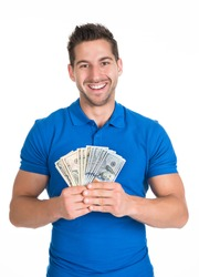 Portrait of smiling young man holding fanned US paper currency isolated over white background