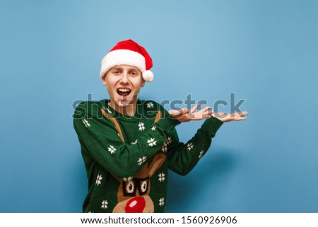 Portrait of smiling young man in santa hat stands on blue background with smartphone in hand, looks into camera and shows OK gesture. Isolated. Copy space Copy space