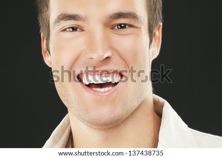 Portrait of smiling young man in white shirt close up, isolated on black background.