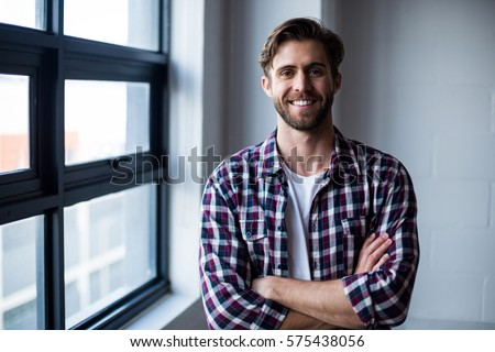 Portrait of smiling young man standing by window in office