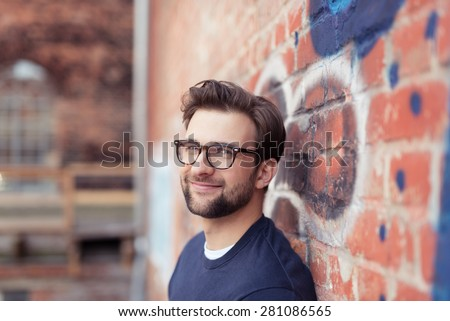 Portrait of Smiling Young Man with Facial Hair Wearing Eyeglasses and Leaning Against Brick Wall Painted with Graffiti
