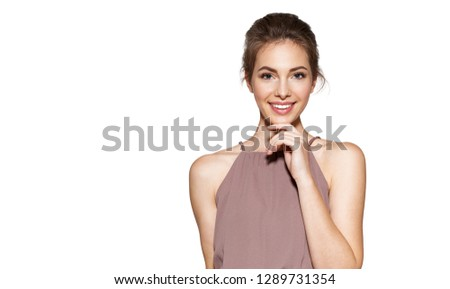 Portrait of smiling young model posing indoors on grey background. Natural beauty and happiness concept. Pretty gilr in trendy dress. Copy space in left side