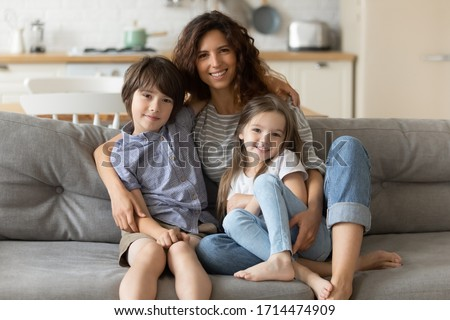 Portrait of smiling young mommy embracing little son daughter, relaxing on couch in studio living room. Positive female babysitter cuddling small children siblings, sitting on sofa, looking at camera.