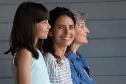 Portrait of smiling young 30s Latino woman with little daughter and elderly grandmother pose on grey background. Three generations of women in row, adult grownup female with child and grandparent.