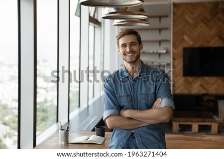 Portrait of smiling young successful Caucasian businessman stand pose in modern office show leadership. Happy man employee or worker feel motivated confident at workplace. Recruitment concept. Foto stock ©