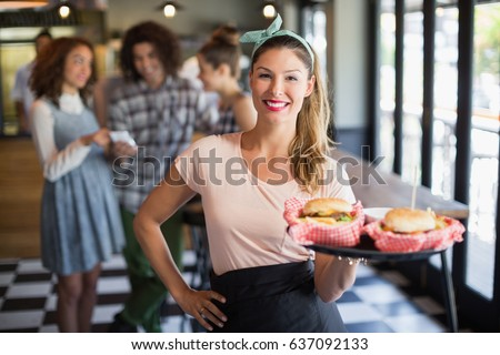 Portrait of smiling young waitress serving burger with customers in background at restaurant #637092133