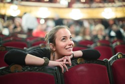 Portrait of smiling young woman in auditorium of theatre