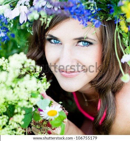 Portrait of smiling young woman in flower wreath at the green forest