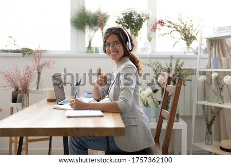 Portrait of smiling young woman in headset sit at desk studying show thumb up recommend online course, happy millennial female give recommendation to distant training or class, education concept