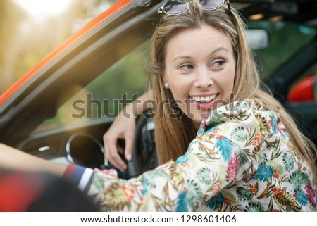 Portrait of smiling young woman in red convertible car #1298601406