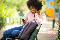 Portrait of smiling young woman sitting on park bench and looking at mobile phone