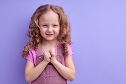 Portrait of sneaky scheming little girl in casual wear thinking over cunning prank and smirking, disobedient child having sly tricky plans in mind. indoor studio shot isolated on purple background
