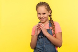 Portrait of sneaky scheming little girl in denim overalls thinking over cunning prank and smirking, disobedient child having sly tricky plans in mind. indoor studio shot isolated on yellow background