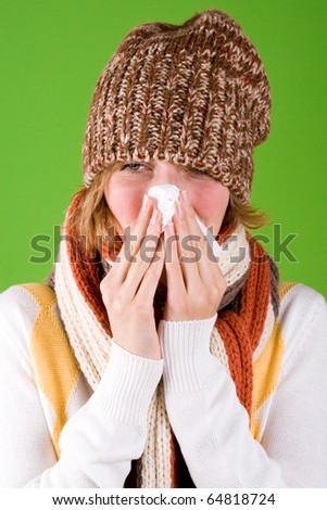 portrait of sneezing woman with handkerchief on green background ...