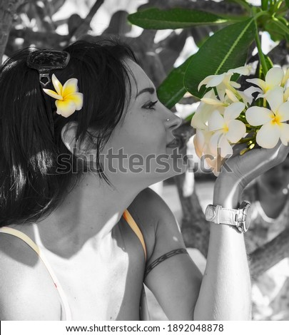 portrait of sniffling  woman with plumeria (frangipane) . beauty concept. close up Stock photo ©