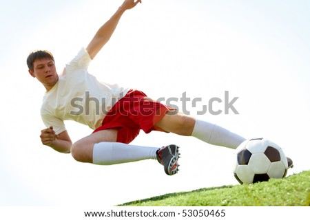 Portrait of soccer player making flying kick at ball during game