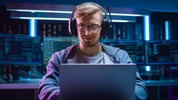 Portrait of Software Developer / Hacker / Gamer Wearing Glasses and Headset Sitting at His Desk and Working / Playing on Laptop. In the Background Dark High Tech Environment with Multiple Displays.
