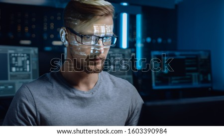 Portrait of Software Developer / Hacker Working on Computer, Projected Code Numbers and Characters Reflect on His Face. Dark Room Full of Electronics, Computers, Displays. Hacking or Programming