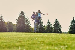 Portrait of soldier is holidng his daughters. Father im military uniform is walking with two little kids on the grass.