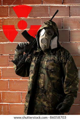 portrait of soldier with camouflage and gas mask against grunge bricks wall with radioactive symbol