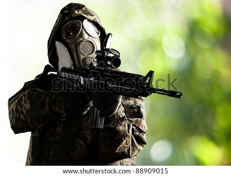portrait of soldier with gas mask aiming with rifle against a nature background
