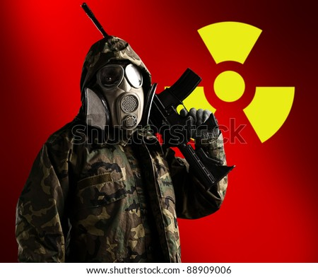 portrait of soldier with rifle and gas mask with radioactive symbol as a background - stock photo