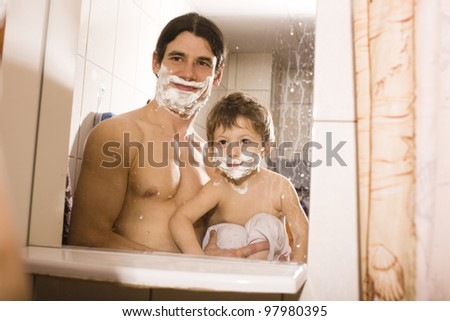 Portrait of son and father enjoying while shaving together