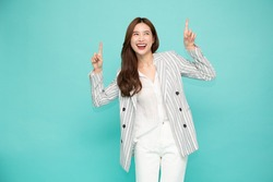 Portrait of Southeast Asian business woman smiling and pointing finger to upper empty copy space isolated on green background, One person of horizontal orientation