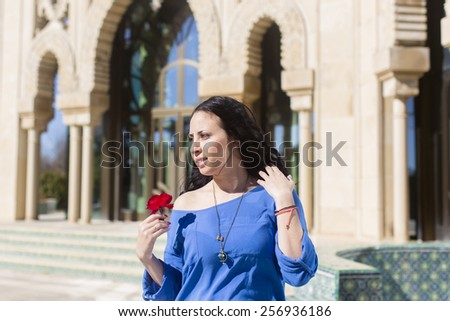Portrait of Spanish young adult woman with big red rose