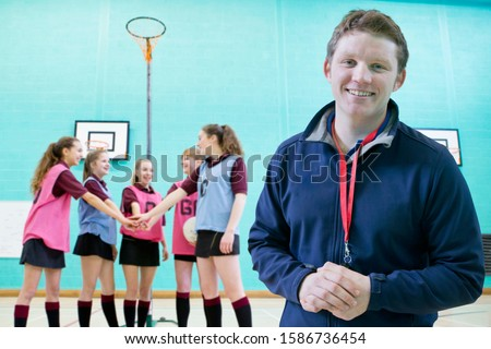 Portrait Of Sports Coach With Pupils Standing In Gymnasium