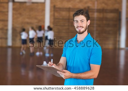 Portrait of sports teacher writing on clipboard in basketball court at school gym #458889628