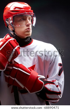 Portrait of sportsman in hockey uniform over black background