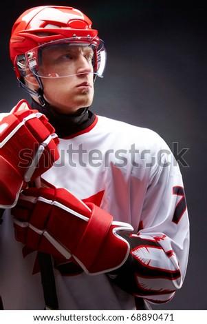Portrait of sportsman in hockey uniform over black background