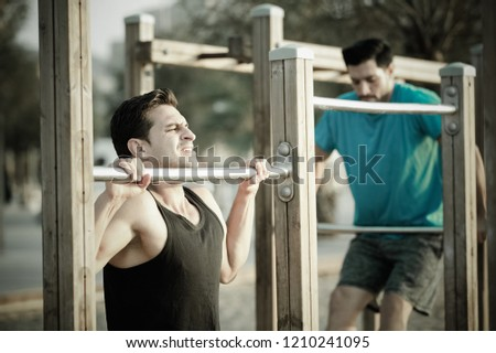 Portrait of sportsmen who are pulling-up in the park near sea.