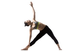 Portrait of sporty fit beautiful young brunette woman in sportswear bra and black pants working out, doing Utthita Trikonasana, Extended Triangle pose, studio full length, isolated, white background