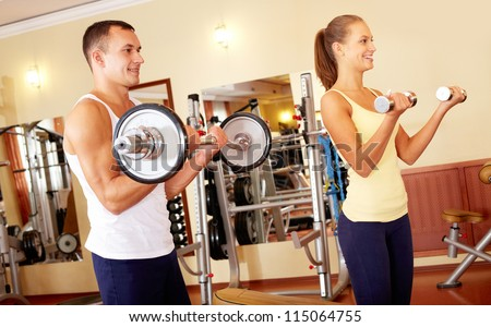 Portrait of sporty man and woman training with barbells