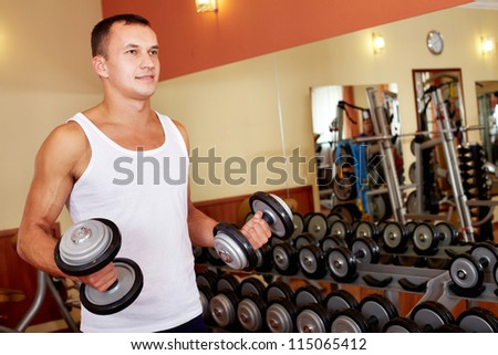 Portrait of sporty man holding two barbells and doing exercise