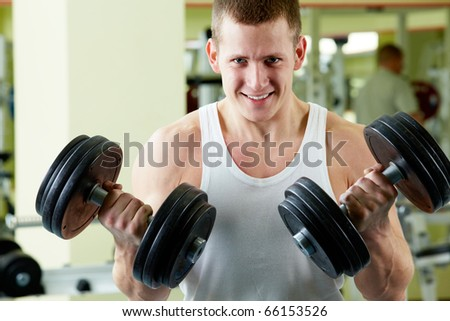 Portrait of sporty man with two dumbbells looking at camera