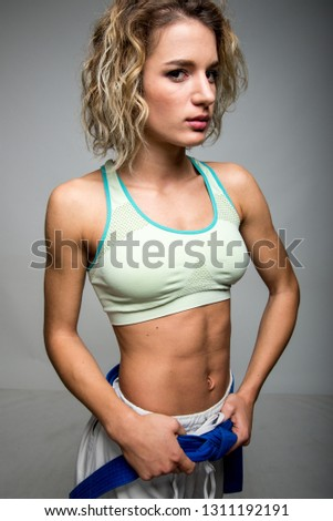 8bacf5474ca22 Portrait of sporty young woman wearing bustier holding blue belt camera  looking on gray background