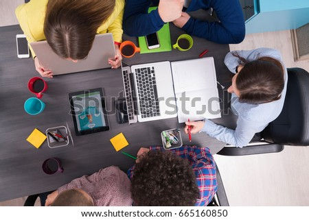 Portrait of startup group of creative people having a meeting with a laptop in a modern office. Business people having relaxed conversation over new project in coworking space #665160850