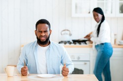 Portrait Of Starving Angry Black Man Waiting For Food At Table In Kitchen, Hungry African American Husband Sitting With Empty Plate And Looking At Camera, His Wife Cooking Lunch On Background